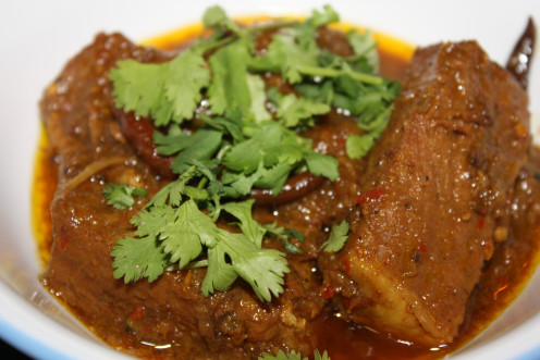 Fiery hot Pork Vindaloo served with coriander leaves on top.