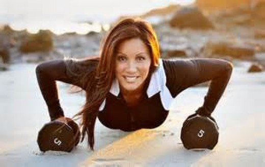 Kiana Tom in long sleeve workout top smiling in push up position with two barbells