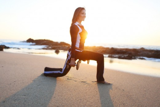 Kiana Tom working out with barbells on a beach at sunset in black and white long sleeves and long pants in