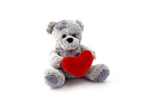 Image of a grey  teddy bear with a red heart symbol in its arms