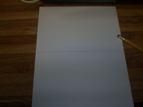 Use a ruler to divide the paper in half.