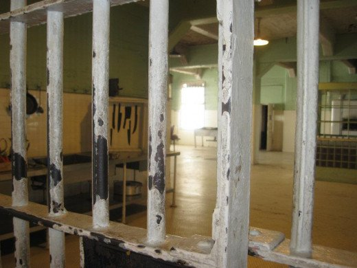 Through the bars on the left, the board with the black knife silhouettes can be seen.