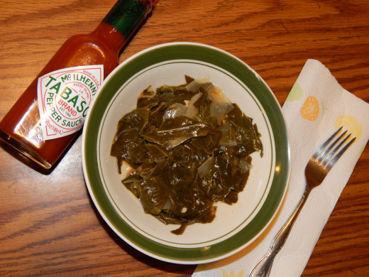Bowl of fresh collard greens from the garden served with Tabasco sauce.