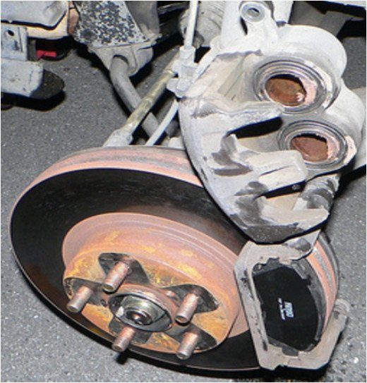 This two piston floating caliper rides on two pins. Install the pads in the torque plate and slide the caliper over the pads.