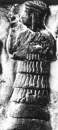 "Close up of limestone disc unearthed by archeologists in 1927. Enheduanna oversees a sacred purification and libation ceremony. She is standing with one arm raised before the face in a Sumerian gesture of greeting aka ""to let the hand be at the nose."