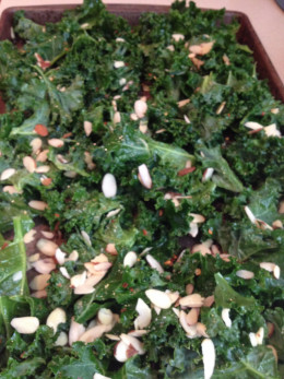 Your kale will shrink in size once you have baked them.  Here I sprinkled almonds in with the bunch.  Excellent flavor result!