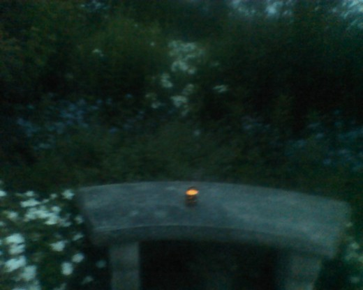 Firefly lantern at dusk on a stone bench in Tower Hill Botanical Garden