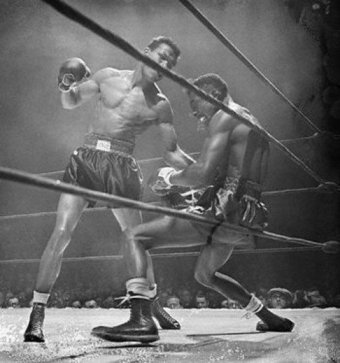 Sugar Ray Robinson is seen here landing a pulverizing left hook to the body of Tommy Bell in their welterweight title bout.