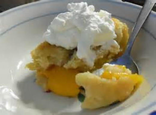 Peach Cobbler served with whipped cream.