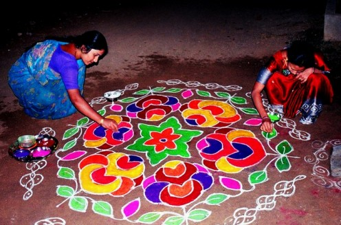 Women filling in vibrant colours on a RANGOLI in front of their doorway as a sign of welcome on Ugadi Day.