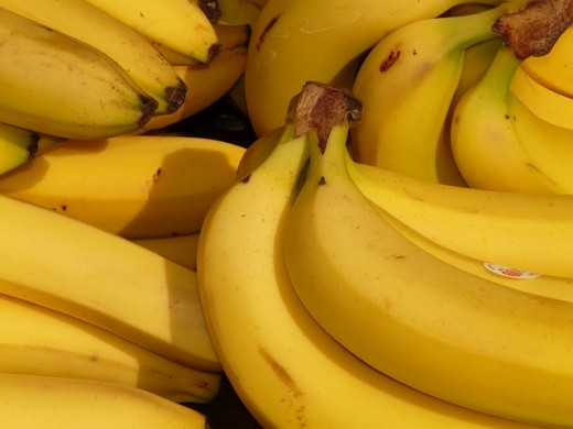 The bananas are transported around the world too be sold in grocery stores to consumers.