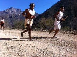 Mile 15 of the race, a young and and old Raramuri are running together.