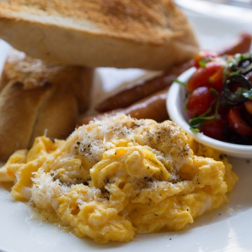 Scrambled eggs with grated cheese, a tomato salad and toasted baguette