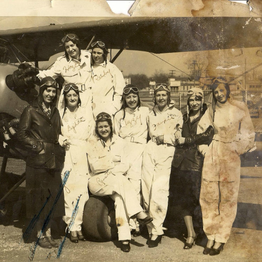 "Photo from an album of my grandmother's belongings. The women of the Squadron of Death, taken in the early 30s in Akron, Ohio. My grandmother, Jessie ""Rusty"" Budrick, aged 20-21, is the one seated on the airplane wheel."