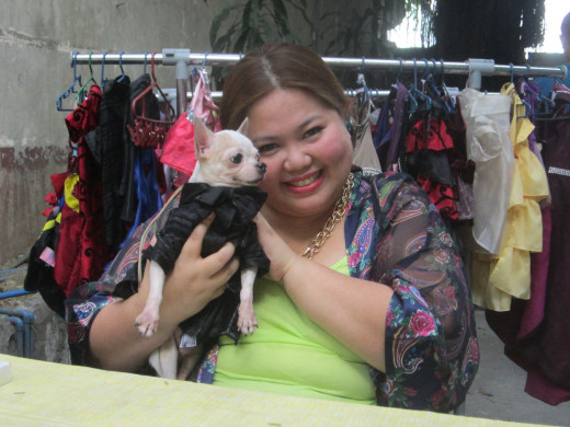 Bernie with a chihuahua wearing one of her creations. More creations can be seen in the rack behind her.