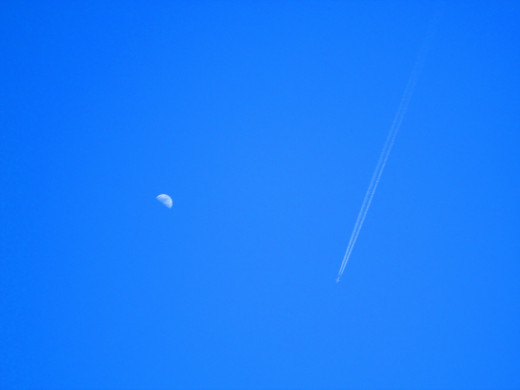 The jet stream is looks amazing against the blue sky, and next to the moon.