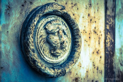 The Ouroboros can be seen in many places...here it's placed on the door to a cemetery encircling the head of a lion.