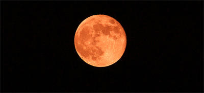The strawberry moon takes on its reddish hue most noticeably when nearest the horizon
