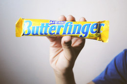 Butterfinger is a candy bar that consists of a flaky, orange colored center that tastes like peanut butter.