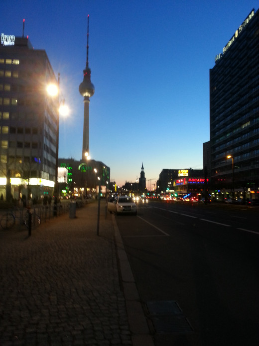 View of the Fernseherturm and Marienkirche, crossing the street in Alexanderplatz just at sunset