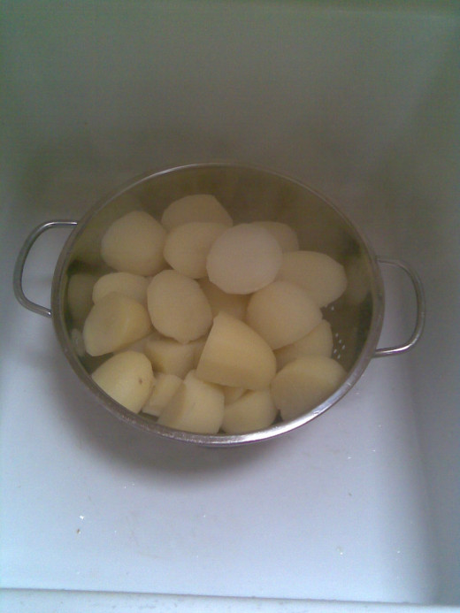 Drain par-boiled spuds.
