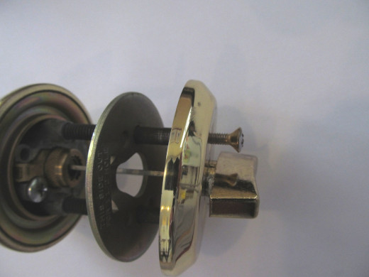 Partially disassembled Arrow D61 deadbolt, side view.  Note how the small screws that hold the interior turnknob escutcheon in place screw directly into hardened steel throughbolts that extend through a hardened steel plate.
