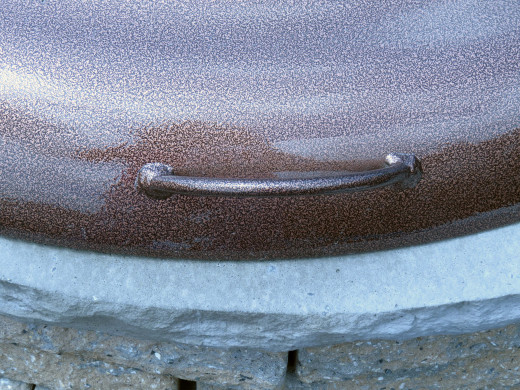 Closeup: One of two side handles on fire pit cover.