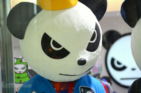 A tough looking Panda wearing a yellow hat starring into a mirror. Representing quality standards.