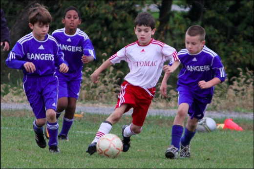 Elementary school age boys playing soccer together.