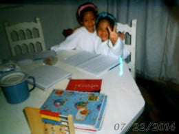 Me and my twin sister, Jennifer doing our homework in our school uniform, you can tell our uniform was all white and clean.
