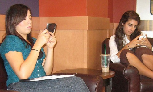 Cell phones are part of everyday life. Two women text messaging, California State University.