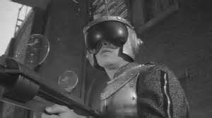 Two future soldiers battle one another. They're struck by a powerful lazer beam that creates a time vortex. A fierce Quarlo soldier returns to 1964. He's under government observation
