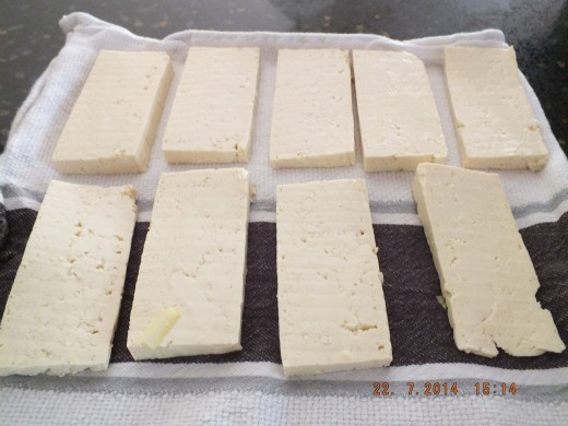 Place the cut tofu onto a clean dry tea towel and place another clean dry towel on top.