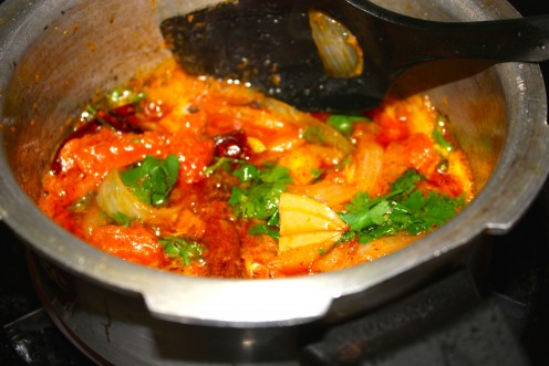 In the remaining oil add 1 tablespoon of ghee. Temper it with green cardamoms, cloves, cinnamon, anise star, pepper corns, mace, bay leaves and dry red chili. Next sauté onions, tomato, ginger-garlic paste. Add coriander- mint leaves and fry well.