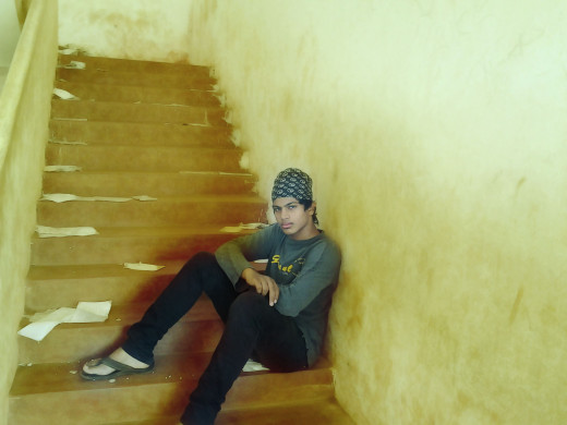 Indian school boy sat on the stair of the High School
