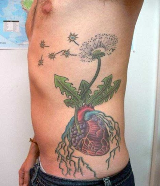 Very unique heart tattoo with nerves or roots with a blooming flower.