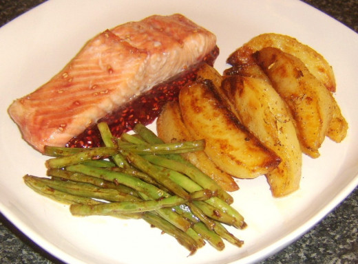 Broiled (grilled) salmon fillet served on raspberry and heather honey sauce with innovatively prepared roast potatoes and green beans