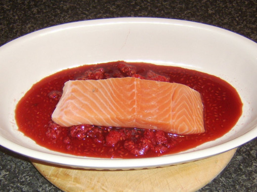 Salmon fillet is laid in raspberry marinade
