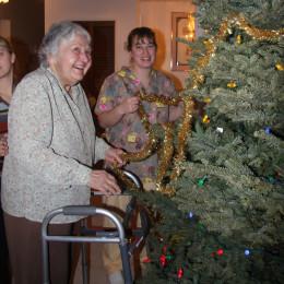 Disable senior decorating a Christmas tree.