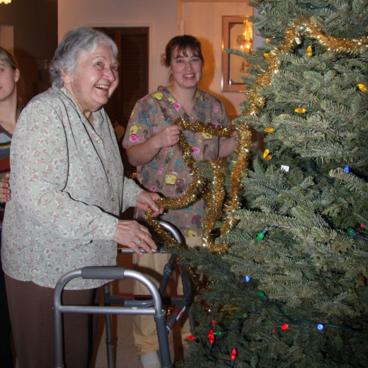 Disable senior decorating a Christmas tree.