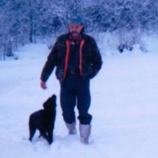 Man taking the family dog for a walk in the winter snow.