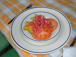 This unusual salad or dessert includes star fruit, tomato slices and pomegranate.