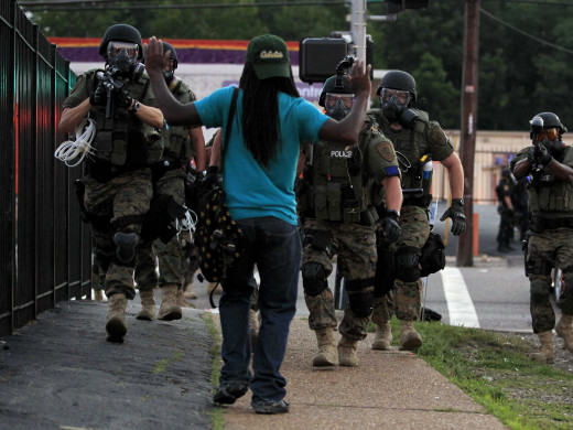 An African-American man during the Ferguson Riots on Monday, Aug. 11 faces an approaching SWAT team armed with assault weapons with his hands in the air.
