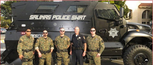 A local police department's SWAT team standing in BDUs with an painted armored vehicle known as an MRAP behind them.