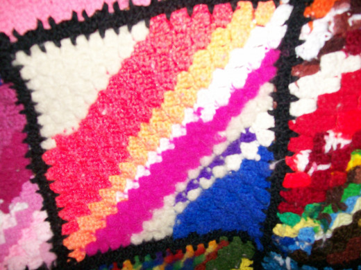 White yarn in the top left corner - felted after washing. The rest of the square is made with acrylic yarn.