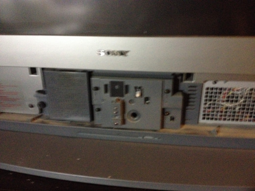 The front panel removed reveals the lamp cover seen on the left.