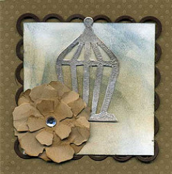 The Chipboard Birdhouse is Heat Embossed With Pewter Powder.