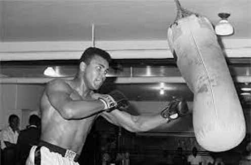 Muhammad Ali is working out on the heavy bag during training for an upcoming fight. The heavy bag is for working on combinations and power punching.
