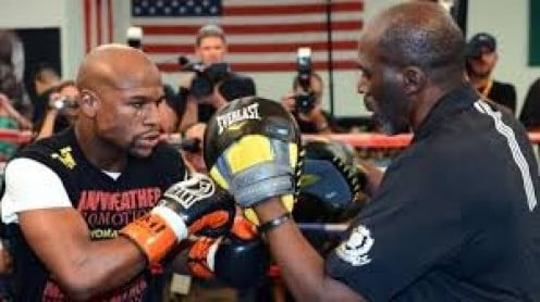 Floyd Mayweather Jr. is seen here training with Roger Mayweather. The two are working with punch mitts which is when you work on strategy with your head trainer.