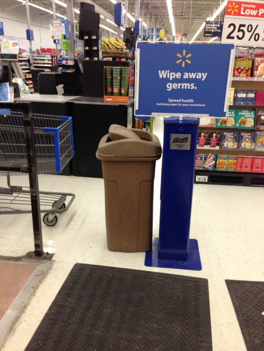 The wipes should be prominently displayed NEAR the carts. They are not much good to you after you entered the shopping area of the store pushing your cart. Your hands are already germy.